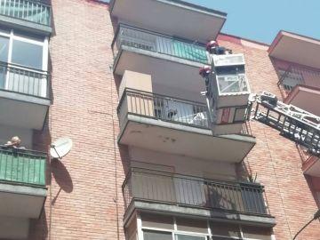 Los bomberos tratan de rescatar a un perro que se encuentra atado al balcón en un día de temperaturas muy altas.