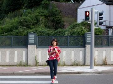El peligro de los 'peatones zombis' para la seguridad vial está obligando a muchos municipios a implantar un sistema de semáforos a pie de acera