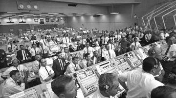 Miembros del equipo del Centro Espacial Kennedy se levantan de sus consolas dentro del Centro de Control de Lanzamiento para observar el despegue del Apolo 11.