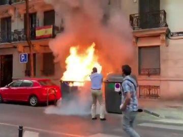 Queman contenedores junto a la sede de Vox y Ortega Smith interviene para apagar el fuego