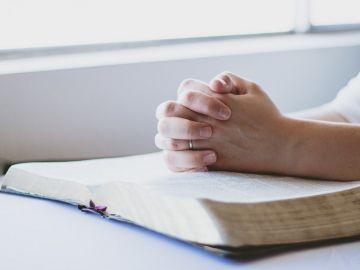Una persona rezando sobre una Biblia