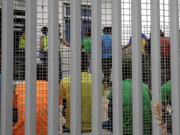Un grupo de migrantes subsaharianos tras el muro del Centro de Estancia Temporal de Inmigrantes