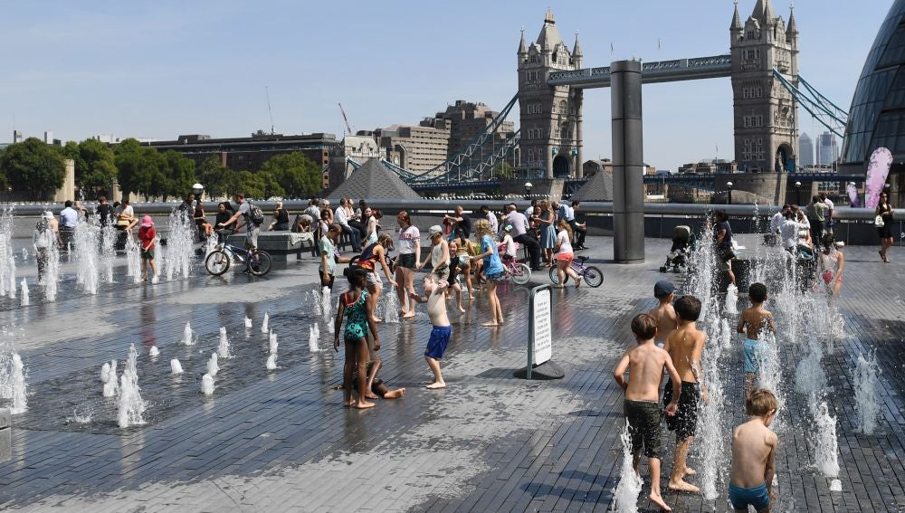Un grupo de niños combaten la ola de calor mojándose en una fuente frente al Puente de la Torre de Londres