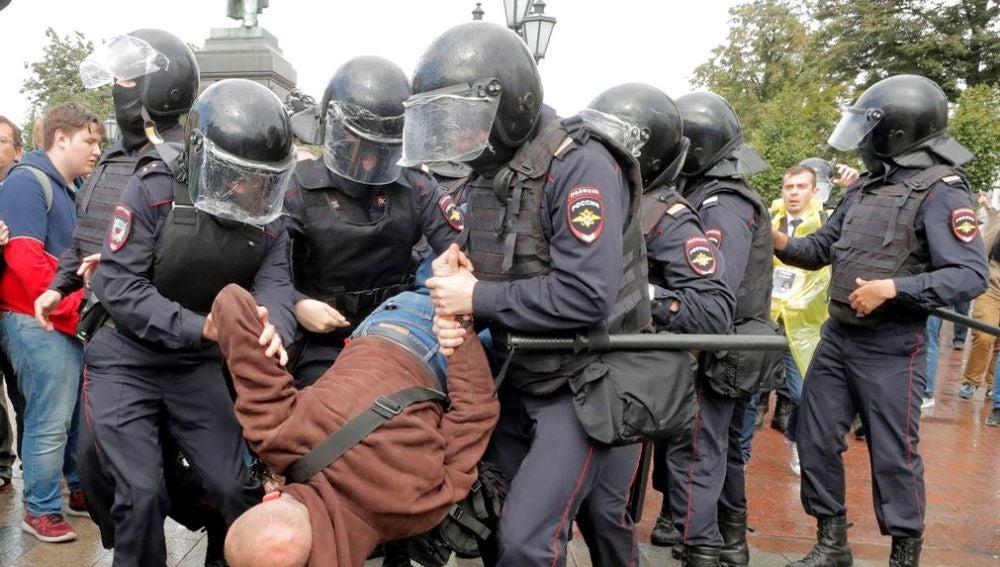 Varios policías antidisturbios se llevan en volandas a un manifestante