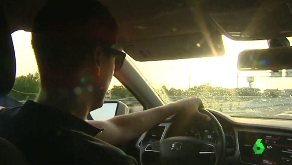 Un hombre en un coche es deslumbrado por el sol