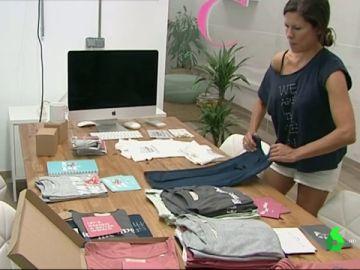 Mujer doblando ropa en una empresa de moda sostenible