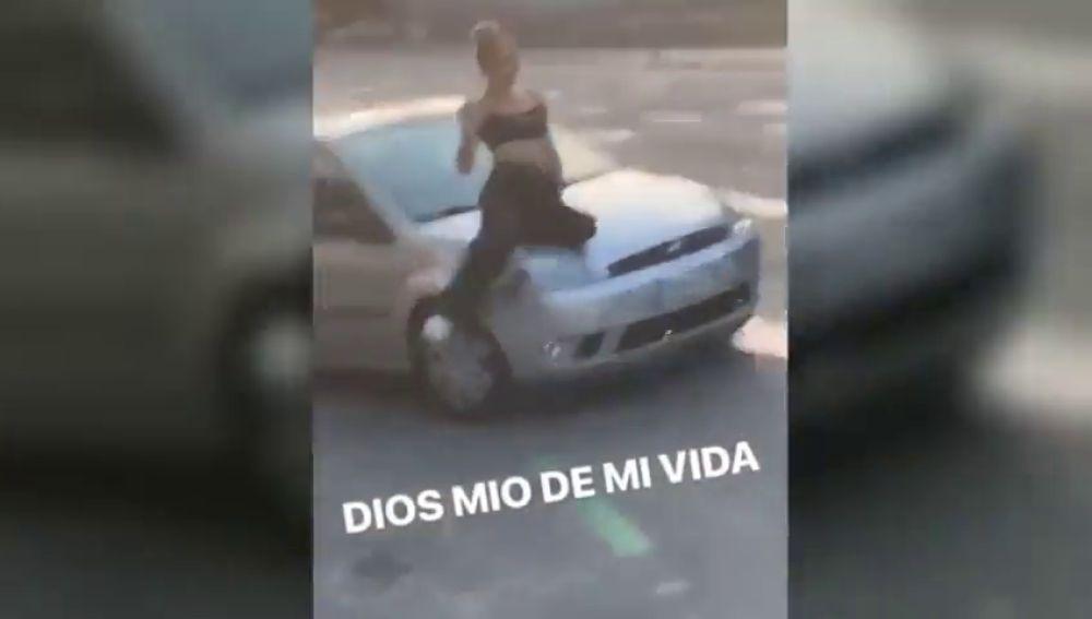 Un conductor temerario transporta a una mujer en el capó de su coche
