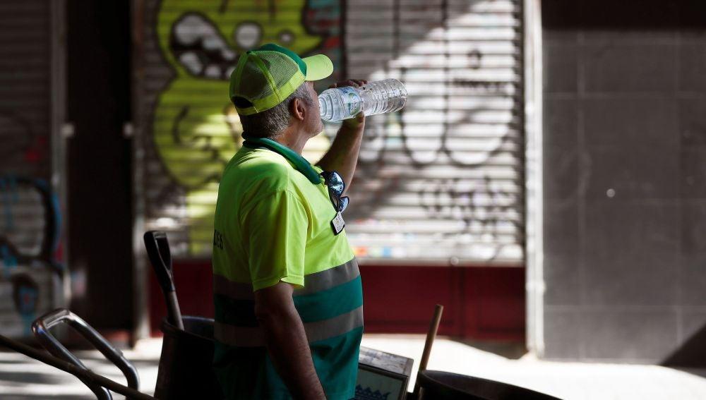 Un trabajador del servicio de limpieza bebe agua en Madrid