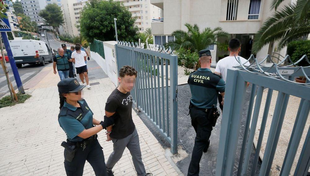 Los cinco investigados entran custodiados al apartamento donde presuntamente tuvo lugar la agresión sexual