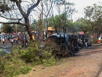Personas congregadas alrededor del camión cisterna incendiado