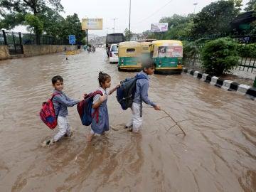Varios niños van a la escuela tras las inundaciones en Nueva Delhi