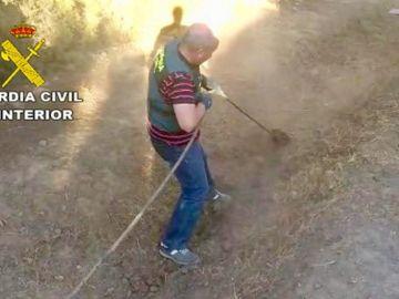 Agente de la Guardia Civil desenterrando la manguera enganchada al oleoducto