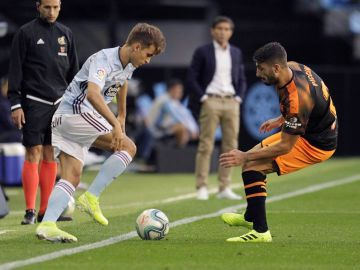 El centrocampista del Celta Denis Suárez (i) pelea un balón con el defensa italiano del Valencia Cristiano Piccini