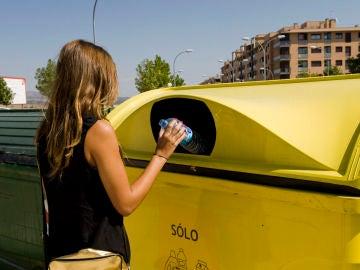Una mujer tira una botella en el contenedor amarillo.