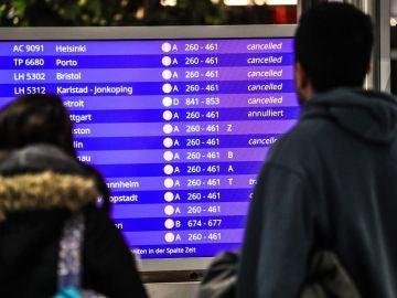Pasajeros miran los vuelos cancelados en una pantalla informativa