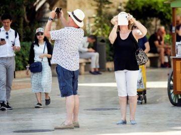 Varios turistas toman fotografías con sus teléfonos móviles, una de las imágenes más habituales que podemos encontrar en estos meses de verano por el centro de la ciudad de Valencia