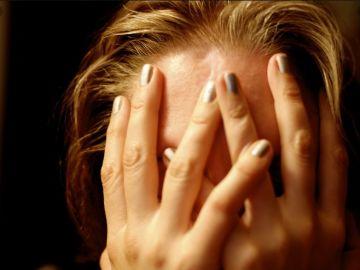 Imagen de una mujer cubriéndose el rostro