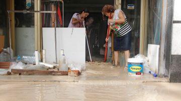 Vecinos de Orihuela limpian sus casas y negocios anegados por la avenida de agua povocada por el desbordamiento del río Segura tras la gota fría.