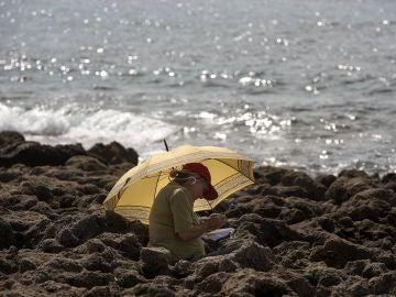 Una persona descansa junto al mar en el municipio de Sant Lluís, Menorca