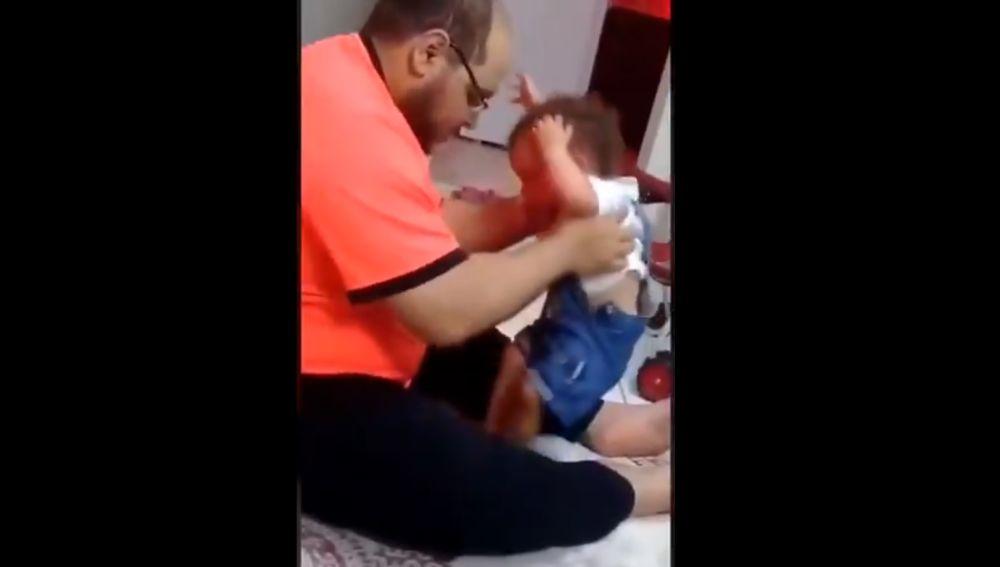 El padre detenido, durante la agresión a su bebé