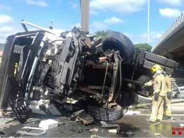 El camión ha quedado destrozado por la caída desde el puente.