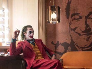 Joker (Joaquin Phoenix) con una imagen al fondo de Murray Franklin (Robert De Niro)