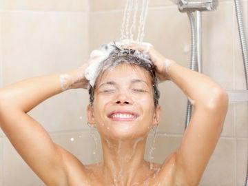 Mujer frotándose el pelo en la ducha