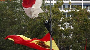 El paracaidista que descendía portando la bandera, en la farola en la que se enganchó