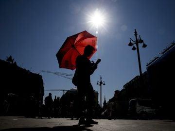 Un joven se protege del sol con un paraguas (Archivo)