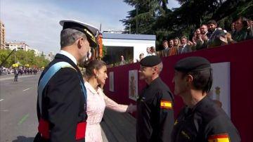 Los reyes saludan al paracaidista que ha chocado contra una farola en el desfile del 12O