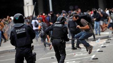 Miembros de los Mossos d'Esquadra cargan contra los centenares de personas que se agolpan ante el Aeropuerto del Prat