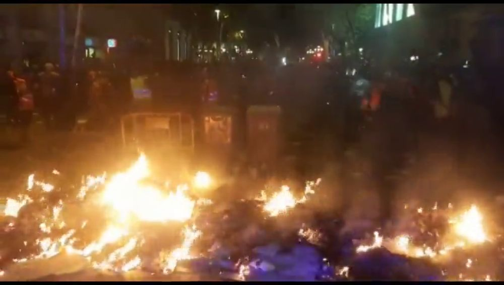 Manifestantes alientan con cartones el fuego de una barricada frente a la Delegación del Gobierno de Barcelona