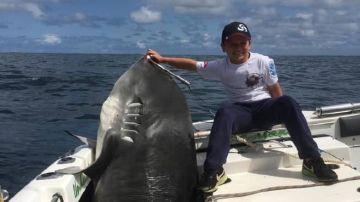 Jayden posa con el tiburón de 314 kilos que capturó
