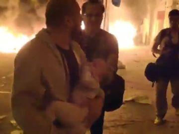 Un padre huye con su bebé en brazos de las llamas de las barricadas en Barcelona