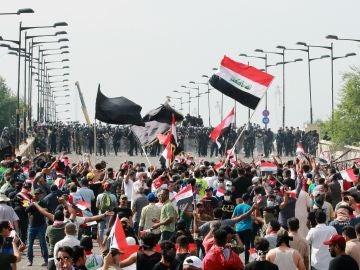 Manifestantes iraquíes portan banderas nacionales mientras gritan consignas