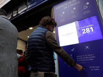 Una persona saca su turno en la administración de lotería Doña Manolita en Madrid