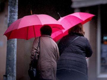 Dos mujeres ser protegen de la lluvia.