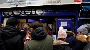 Decenas de personas hacen cola en Doña Manolita para comprar la tradicional Lotería de Navidad