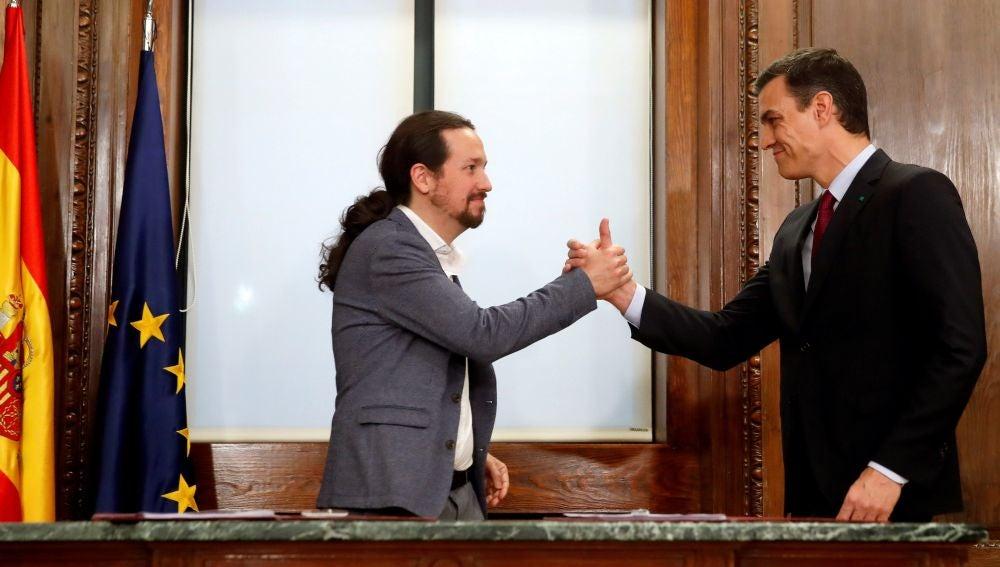 Pedro Sánchez y Pablo Iglesias estrechan sus manos tras el acto de firma del acuerdo programático (Archivo)