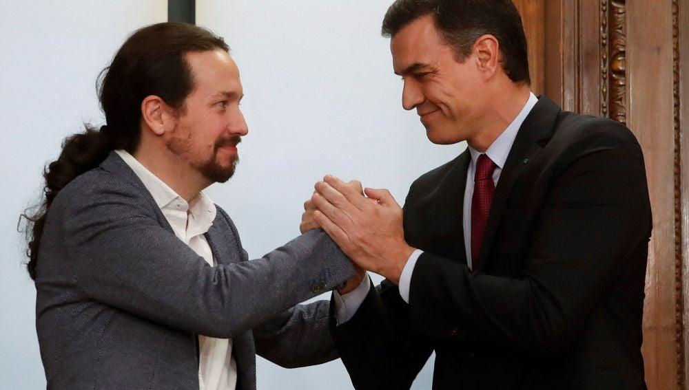 El candidato a la investidura, Pedro Sánchez, y el líder de Podemos, Pablo Iglesias, estrechan sus manos tras el acto de firma del acuerdo programático (Archivo)