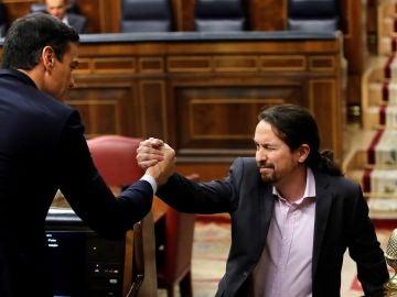 El líder de Unidas Podemos, Pablo Iglesias, saluda a Pedro Sánchez