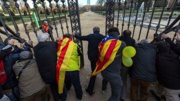 Los manifestantes abren la verja que rodea el Parlament en el Parc de la Ciutadella