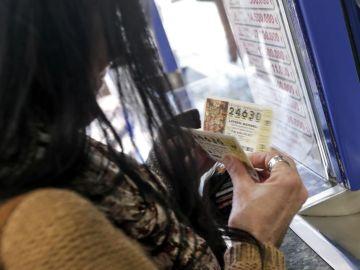 Una mujer compra varios décimos en una administración de Lotería