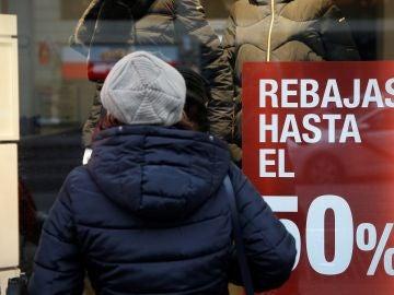 Una consumidora observa el escaparate de una tienda
