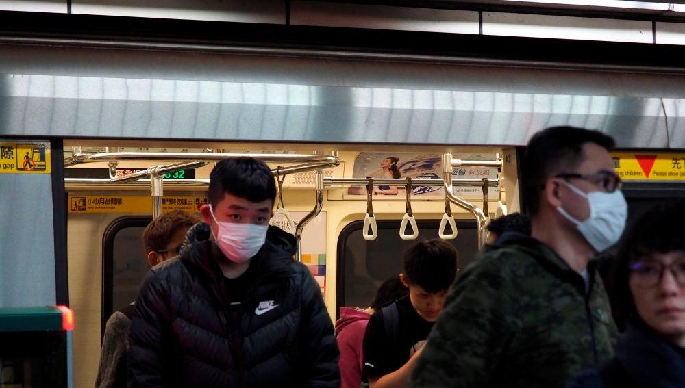 Ciudadanos chinos saliendo con mascarilla del metro