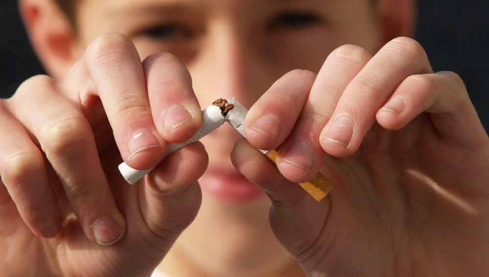 hombre joven rompiendo un cigarrillo