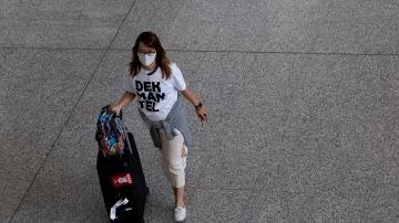 Una mujer con una mascarilla desplazándose con una maleta