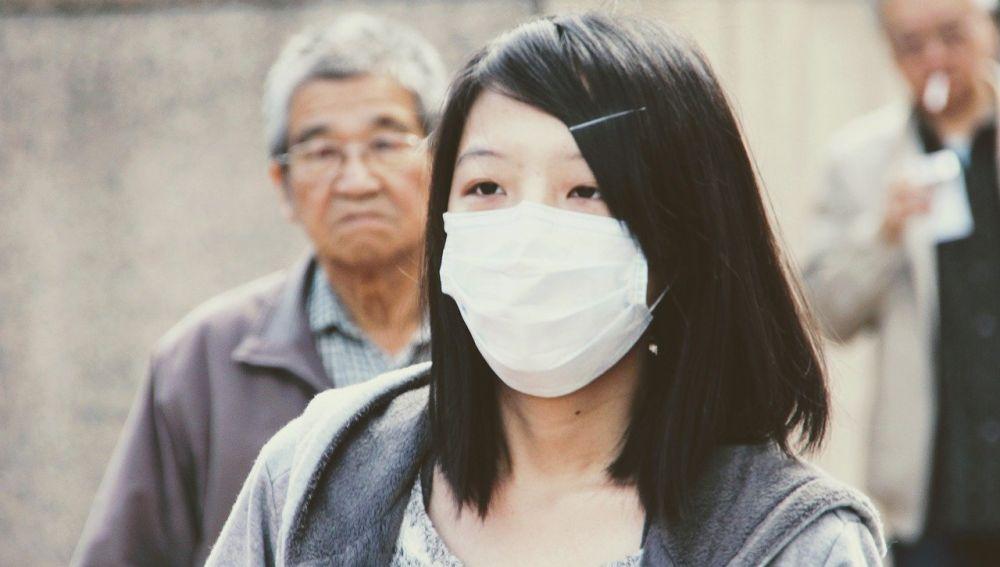 mujer con mascarilla de protección frente al sars