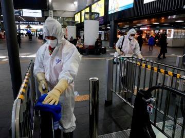 Los trabajadores rocían desinfectante en la estación Suseo en Seúl