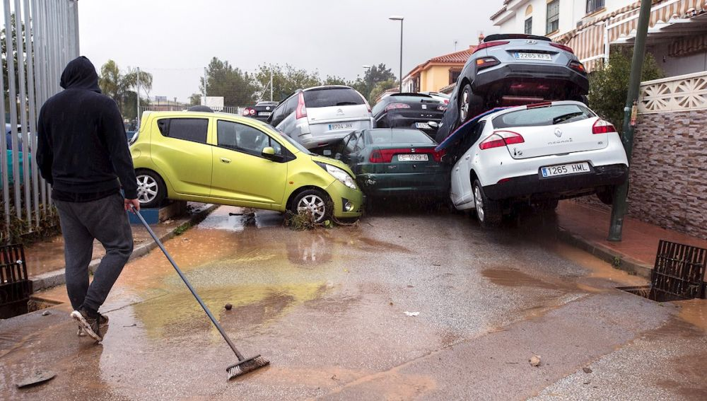 Un hombre limpia la zona y observa los coches amontonados en Málaga
